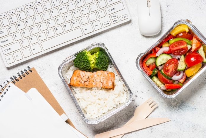 takeout food in front of desktop computer keyboard
