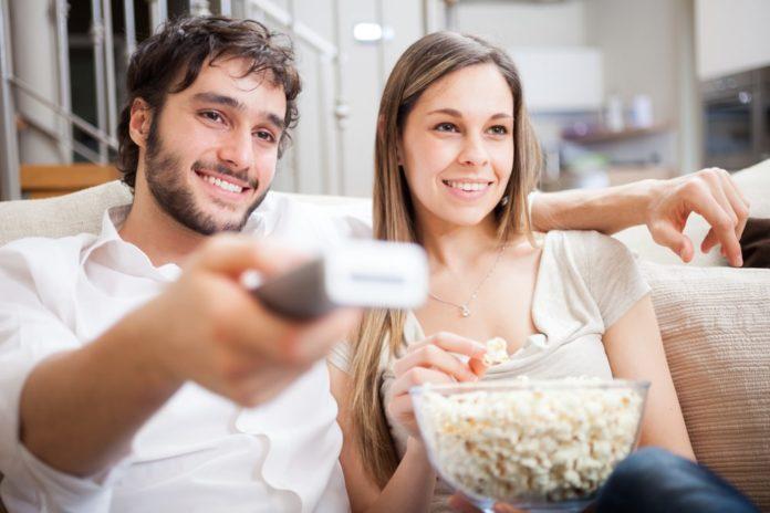 couple watching tv together with popcorn bowl on couch