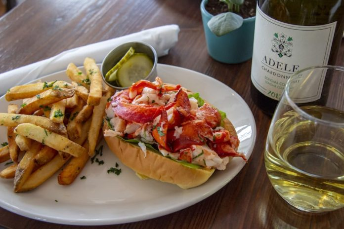 lobster roll on a plate with fries and wine green hill kitchen greenport