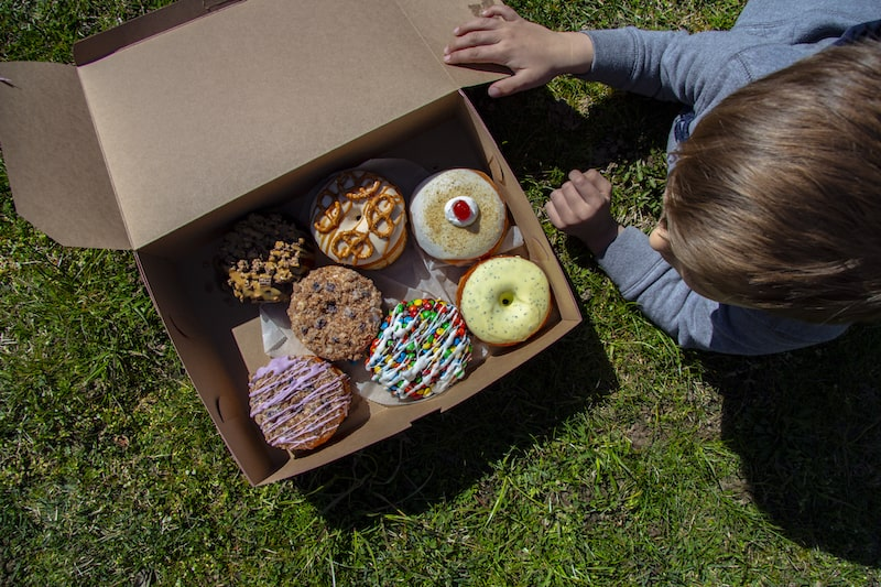 doughnuts in box with a young boy north fork doughnut co