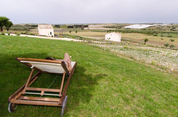 woman sitting on lawn chair overlooking organic farm