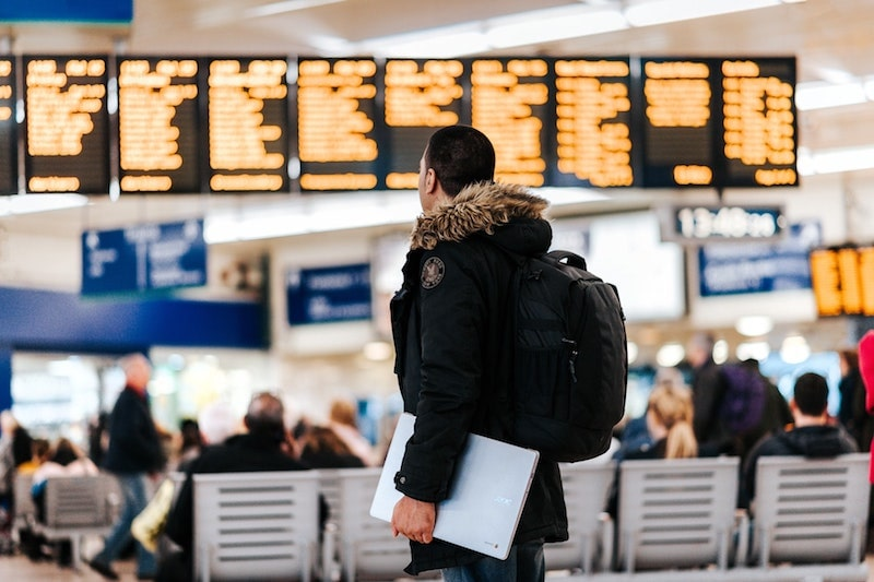 Young man looking at flight roster at airport wearing winter coat