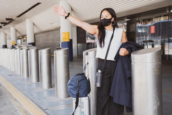 girl traveling at airport pickup wearing black face mask