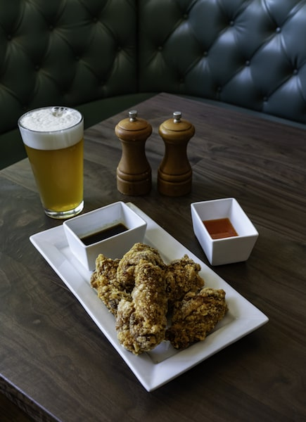 crispy wings and beer on table in rustic tavern salt and pepper shakers
