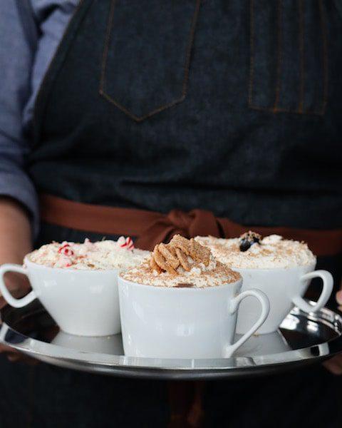 man holding cocktails denim apron festive holiday drinks hot chocolate