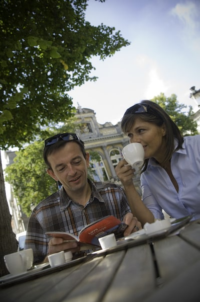 couple drinking coffee and reading travel book outside