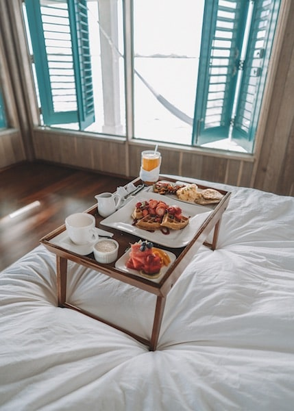 breakfast in bed tropical getaway paradise white sheets open window