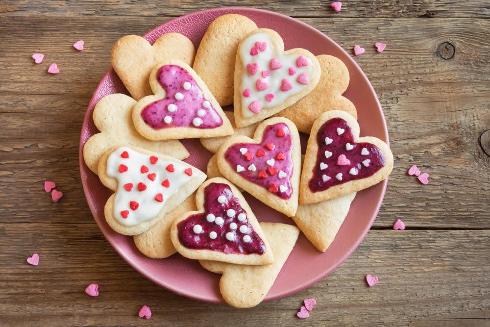 plate of valentine's sugar cookies with pink and white icing sprinkles