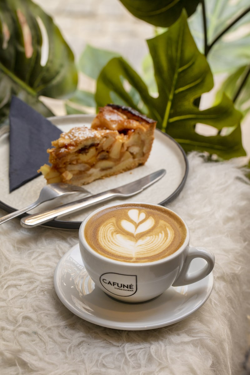 cake slice and cappuccino with latte art painted leaf background