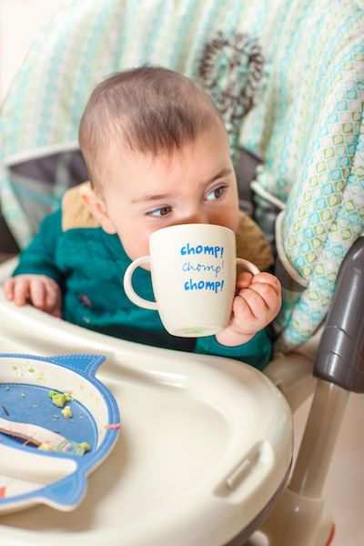 little baby drinking from white mug cup in highchair