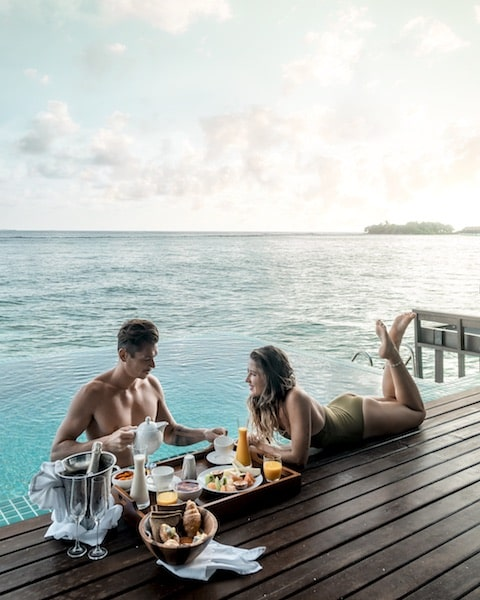 couple at water deck eating breakfast tropical paradise brown hair man woman