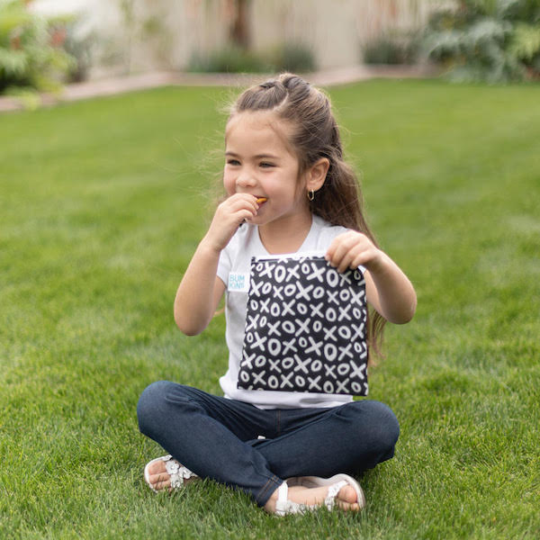 young girl eating snack in green grass