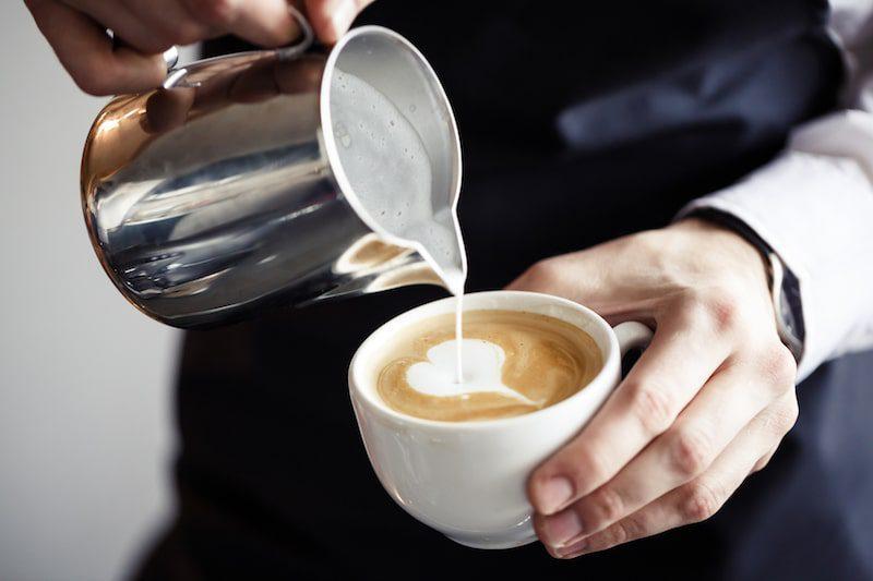 barista making a cappuccino heart shaped foam