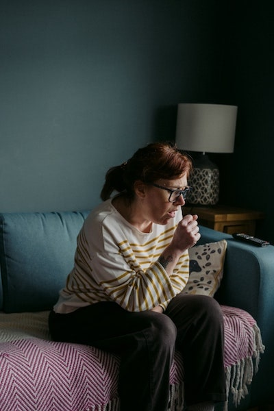 woman coughing in low light room