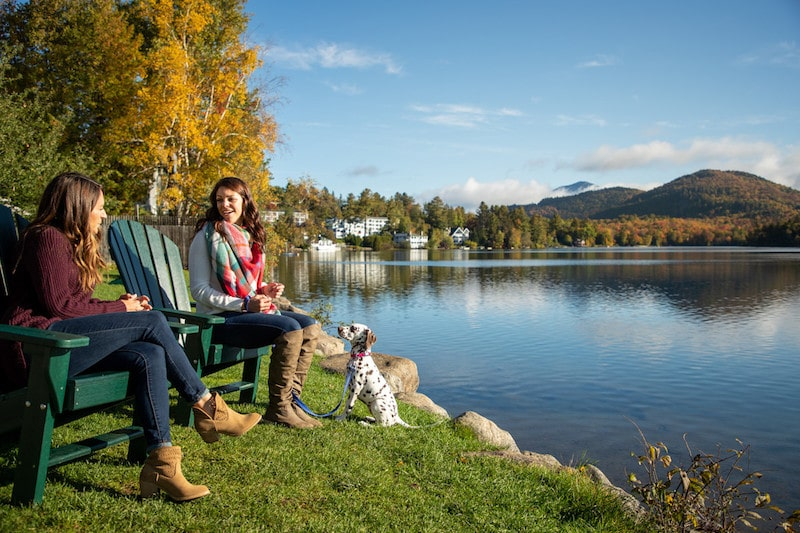 lake placid fall lake with puppy and two people sitting in adirondack chairs