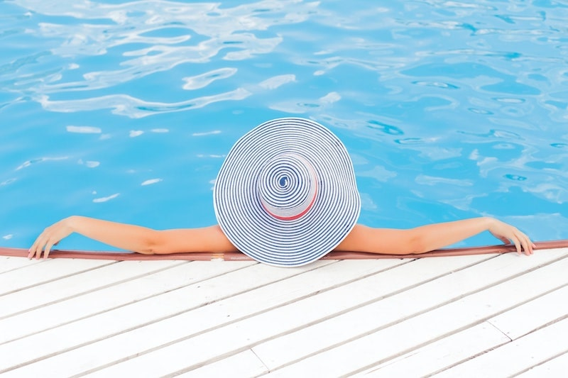 woman lounging by the pool with hat