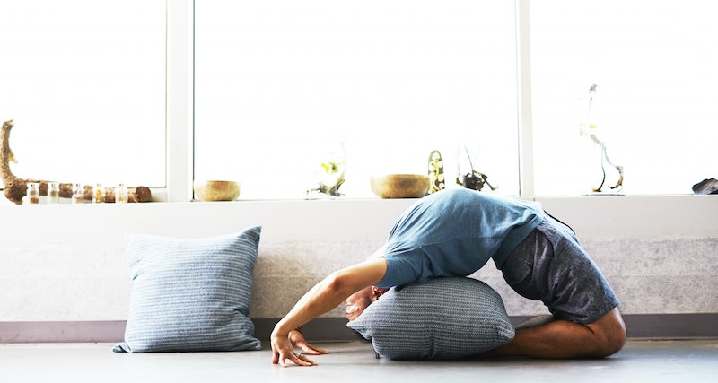 man doing yoga at home using pillow for back support