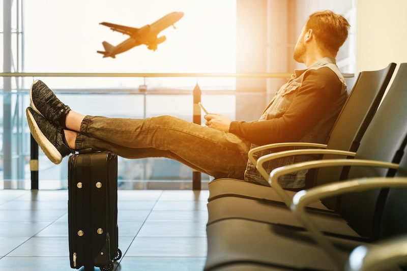 man looking outside at airplane taking off at airport