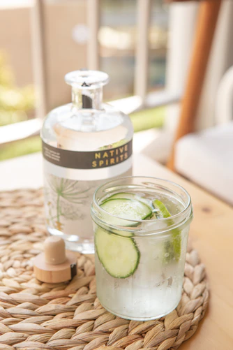 cucumber gin and tonic glass with bottle display