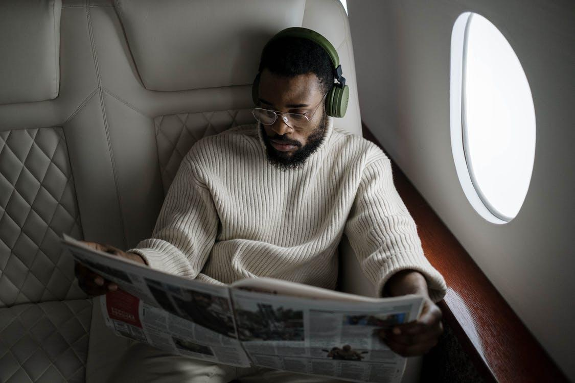 man sitting on plane with white sweater reading newspaper private jet travel east end taste