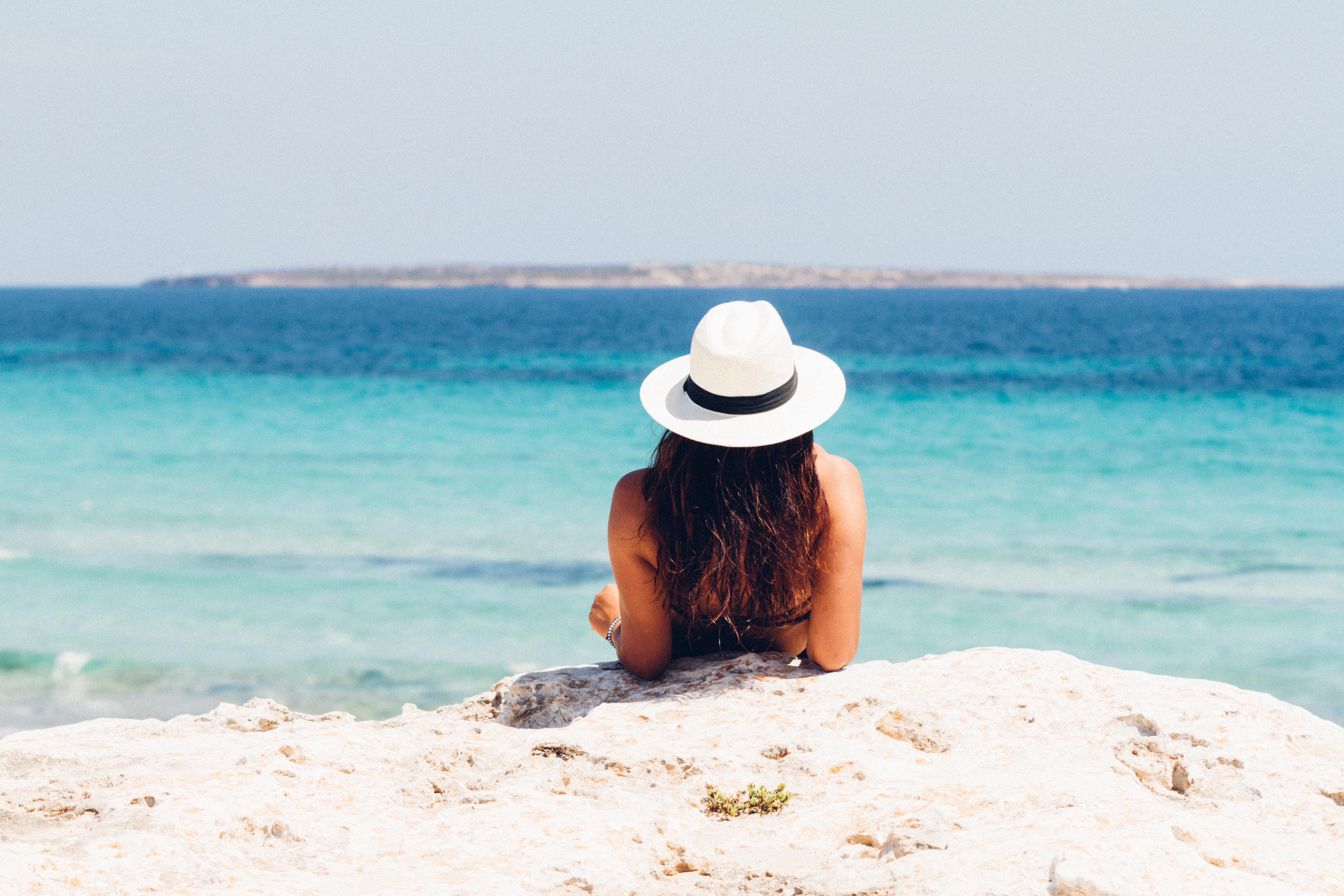 Woman on beach with white hat sand