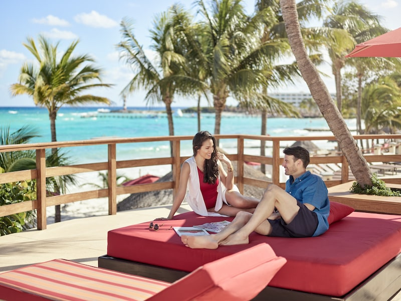 grand club sundeck couple sitting red lounge chairs