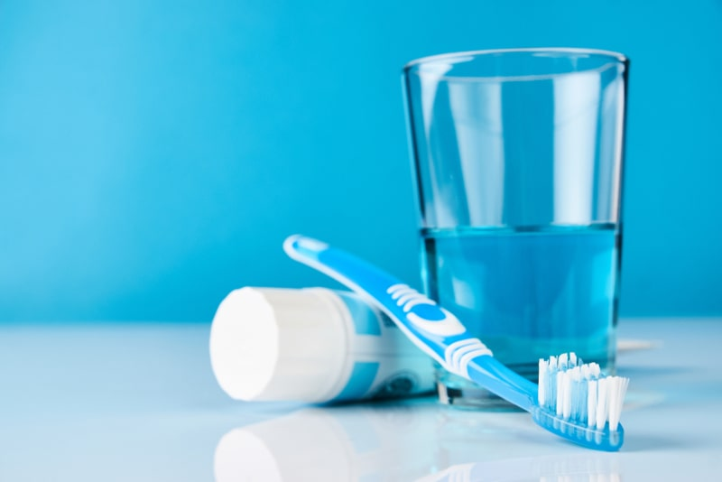 toothbrush toothpaste mouthwash blue tone background