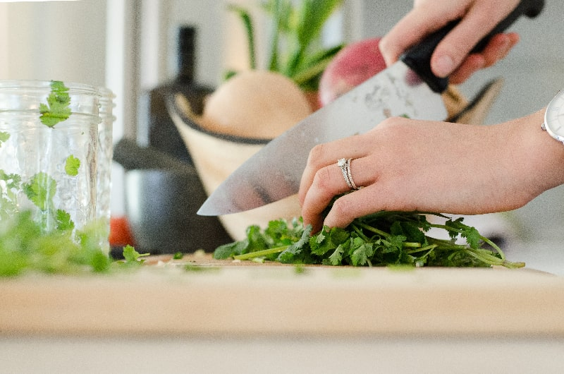 woman cooking and cutting with knife on cutting board